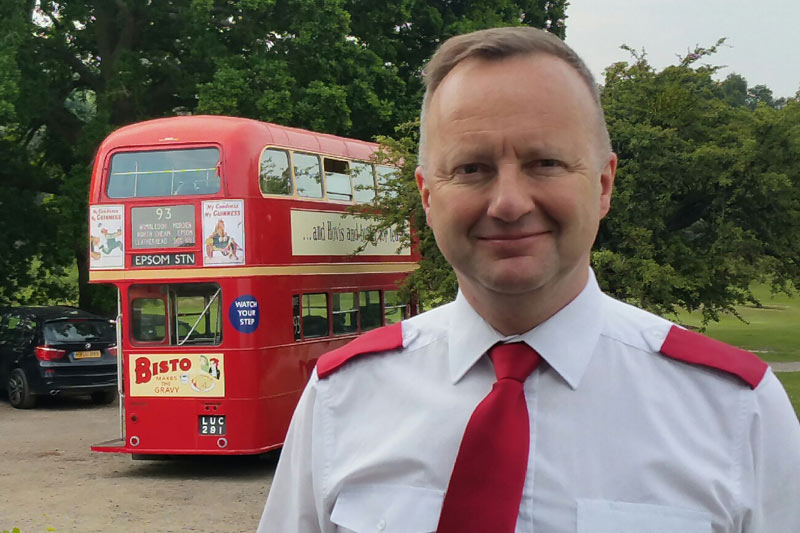 Richard in uniform with the red double deck bus